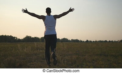 Young man with raising hands running in field and enjoying freedom. Carefree guy running on grass field at summertime. Landscape background. Relaxation on nature. Rear back view
