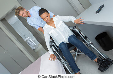 young man with sad girl in wheelchair at home
