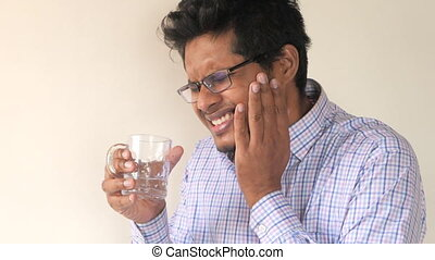 young man with sensitive teeth and glass of cold water