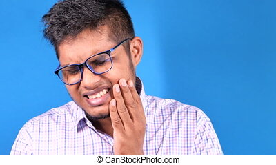 young man with sensitive teeth on blue background .