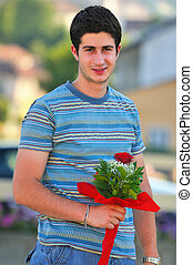 Young man with single rose in his hand