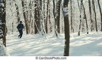 Young man with smart watch or heart tracker running on snow covered winter road in forest