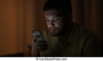 young man with smartphone at night