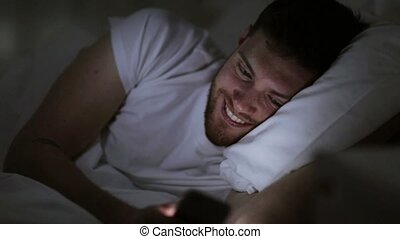 young man with smartphone in bed at night