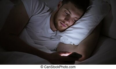young man with smartphone in bed at night - technology,...