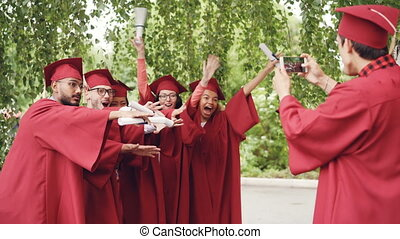 Young man with smartphone is taking pictures of graduates...