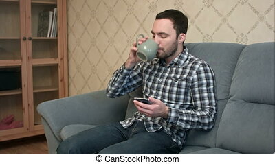 Young man with smartphone sitting on couch at home