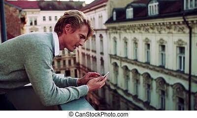 Young man with smartphone standing on a balcony in city,...