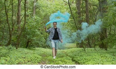 Young man with smoke bomb walking in forest - Handsome male...