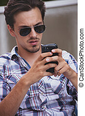 young man with sunglasses and smartphone outdoor portrait