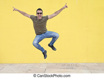 Young man with sunglasses jumping in front of a yellow wall.