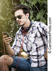young man with sunglasses smartphone and headphones outdoor portrait