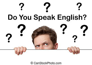 Young man with surprised eyes peeking out from behind billboard paper poster. Man peeking out from the edge and looking at camera isolated on a white background. Do you speak english?