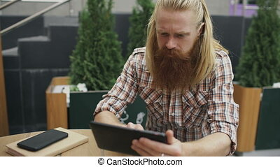 Young man with tablet computer sitting in cafe outdoors having relax and resting of work