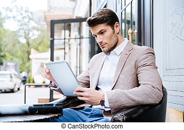Young man with tablet pc touch in a cafe outdoor - Young...