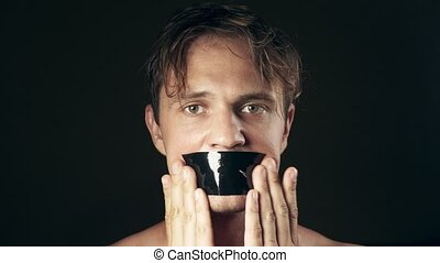 Young man with taped mouth. on a black background. 4k. -...