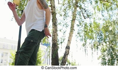 Young man with tattoos freestyle dancing in the park. Mid...