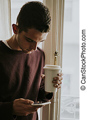 young man with the mobile phone and the cup of coffee in the window