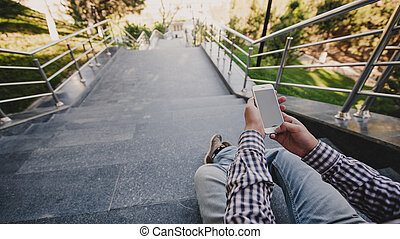 young Man with the phone in his hand sitting on the steps. top view