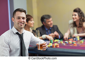 Young man with whiskey looking up from roulette table