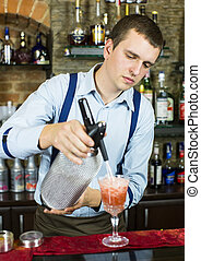 bartender - young man working as a bartender in a nightclub ...