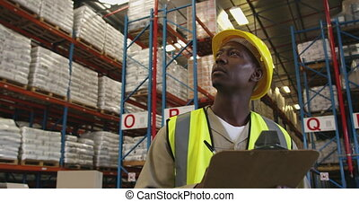 Young man working in a warehouse 4k - Close up front view of...