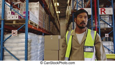 Young man working in a warehouse 4k - Close up of a young ...