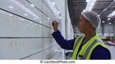 Young man working in a warehouse - Side view of focused ...