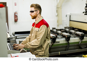 Young man working in furniture factory