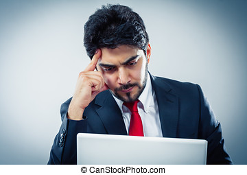 Young man working on a laptop focused