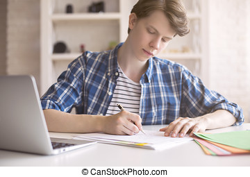 Young man working on coursework - Close up of casual young...