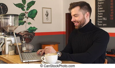 Young man working on his laptop in a coffee shop in morning.