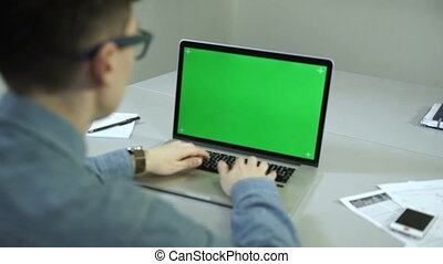 young man working on his laptop in a office. Green screen