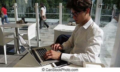 Young man working on laptop computer outside