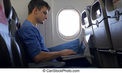 Young man working on laptop in aircraft