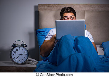 Young man working on laptop in bed