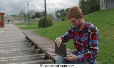 Young man working on laptop in the park