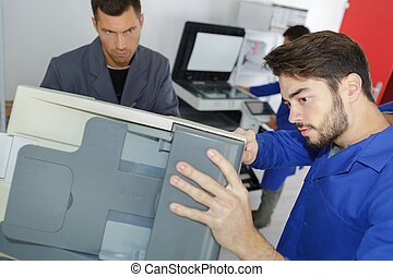 Young man working on office printer