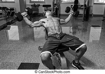 Young Man Working Out Chest With Dumbbells