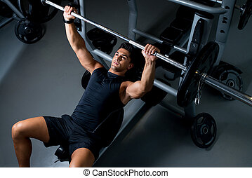 Young Man Working Out in the Gym - Bench Press Workout