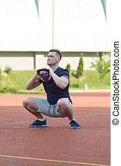 Young Man Working Out With A Kettle Bell