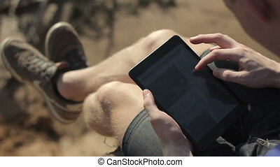 Young man working outdoors with tablet.