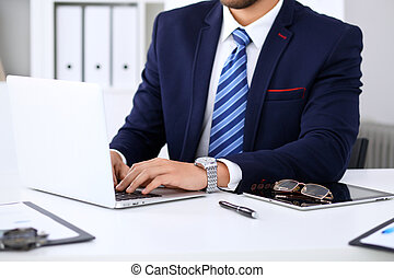 Young man working with laptop computer, man's hands on notebook, business person at workplace