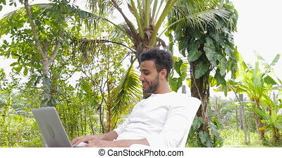 Young Man Working With Laptop Computer Outdoors In Tropical...