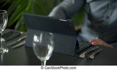 Young man works with his laptop in the cafe close up.