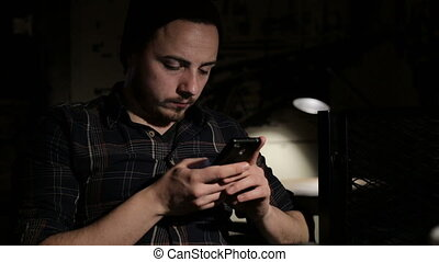 Young man write sms smartphone in cafe in the night