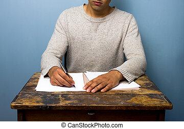 Young man writing at desk