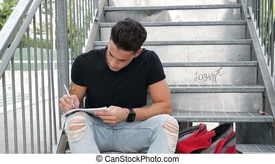Young man writing on paper sheet with pen