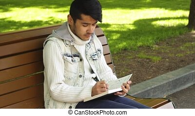 Young man writing something in notebook sitting in the...