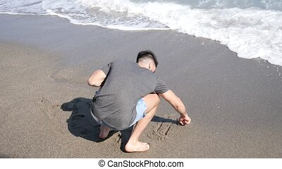 Young man writing Summer on a beach